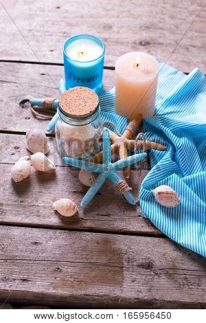 Background with marine items and blue candle on aged wooden planks. Sea objects on wooden planks. Selective focus.