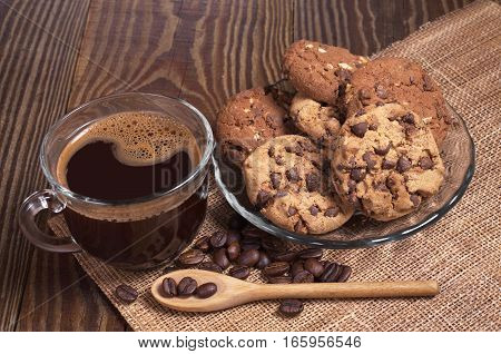 Cup of hot coffee and plated chocolate cookies on wood