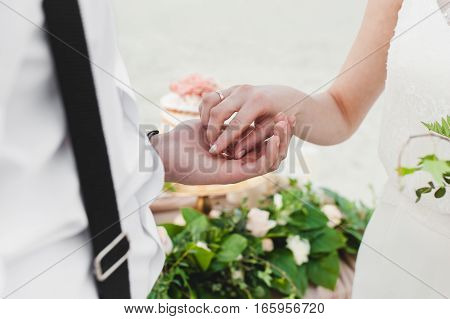 The bride and groom exchange rings outdoors