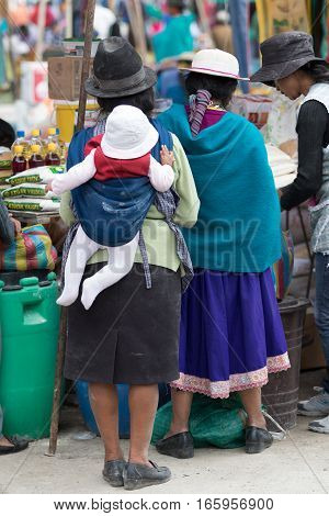 July 24 2016 Alausi Ecuador: indigenous kichwa woman dressed traditionally carrying her child on her back in the local produce market