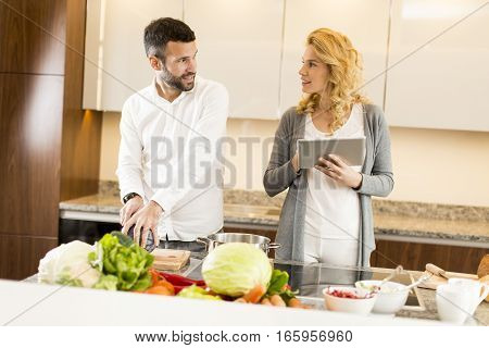 Young Woman Using Tablet At The Kitchen Table While Man Preparing Food