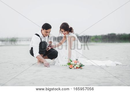 Bride and groom draw on the sand
