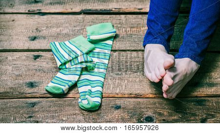 Bare female feet and green striped socks laying on the wooden floor. Closeup view. Selective focus