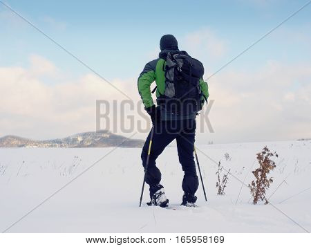 Man With Snowshoes Walk In Snowy Filed. Hiker Snowshoeing  In Powder Snow