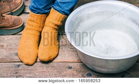 Feet wearing wool socks near basin with warm water on the floor before footbath. Color toning