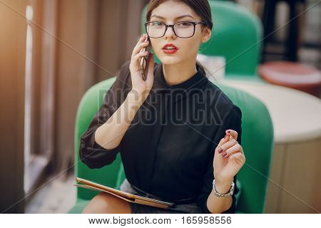beautiful business lady drinking coffee and uses different gadgets