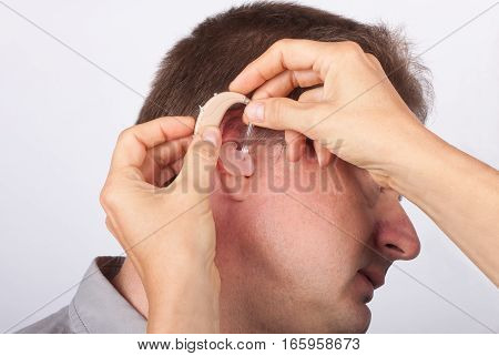 Audiologist fitting a man patient with hearing aid