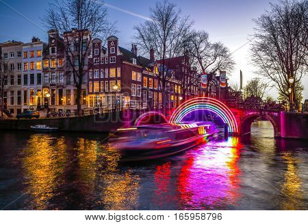 AMSTERDAM NETHERLANDS - JANUARY 10 2017: Cruise boats rush in night canals. Light installations on night canals of Amsterdam within Light Festival. January 10 2017 in Amsterdam - Netherland.