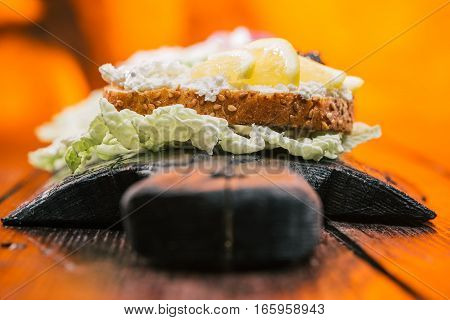 Sandwiches with farmer cheese and lemon. Fire lighting background