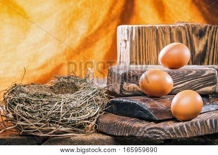 Chicken eggs on stairs of wood serving boards next to bird nest over firelight background