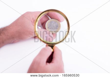 Hand With Euro And Magnified Glass