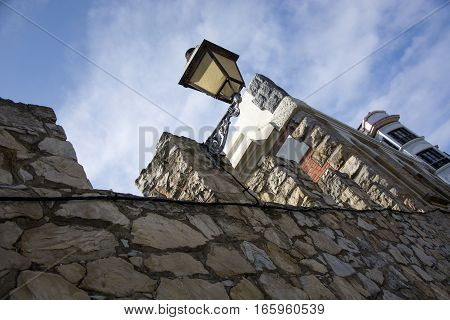 Photo of a streetlight with wall, blue sky and sunlight