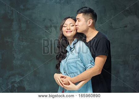 Portrait of smiling Korean couple on a gray studio background