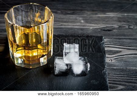 glass of whiskey on dark wooden background close up