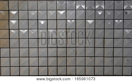 Wall of dirty white tiles reflect light bulbs background.