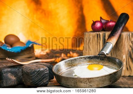 Cooked and uncooked eggs on rustic table over burlap background