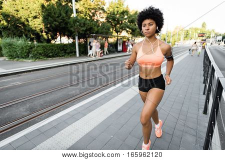 Woman fitness model training outside and listening to music