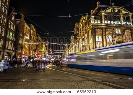 AMSTERDAM NETHERLANDS - JANUARY 08 2017: Amsterdam city night streets with different kinds moving transport & silhouettes of passersby. January 08 2017 in Amsterdam - Netherland.