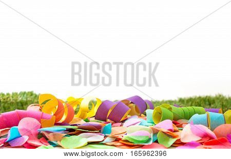 Colorful Confetti And Streamers On Grass In Front Of Background As Template For Celebration And Part