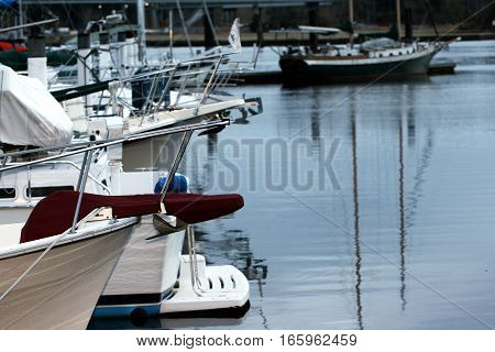 A red seat at the edge of a boat, docked in a harbor