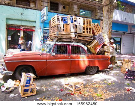 MONTEVIDEO, URUGUAY, NOVEMBER 25th 2011: Red oldtimer packed with wooden crates on street market in Montevideo,Uruguay