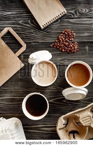 coffee cup take away at dark wooden background top view