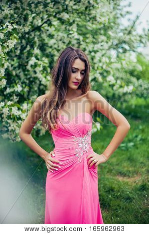 Portrait of young beautiful woman posing among spring blossom trees. Professional make-up and hairstyle. Perfect skin. Fashion photo. Natural beauty.