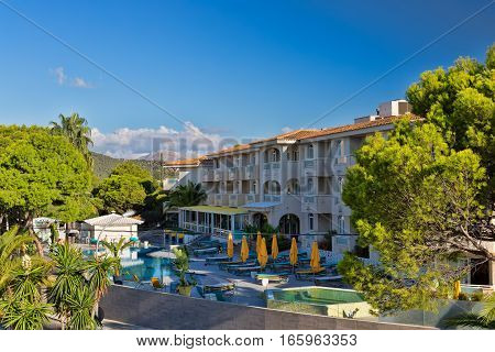 Hotel with swimming pool and palm trees on the background of mountains and blue sky