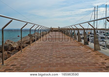 Pier with handrails on the background of yachts masts