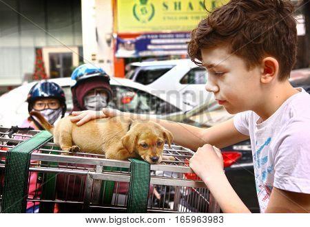 Ho Chi Minh, Vietnam, Januar 15, 2017: Unidentified european tourist boy sightseeing stroke puppy for sale on busy traffic sreet background in Vietnam, Januar 15, 2017.