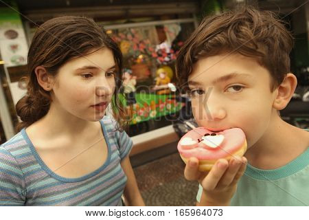 boy and girl with doughnut on street close up photo