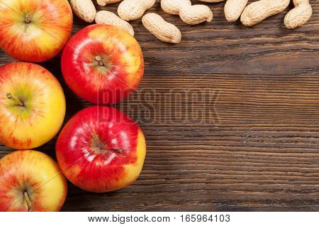 Ripe red apples and peanuts on a wooden background. Top view.