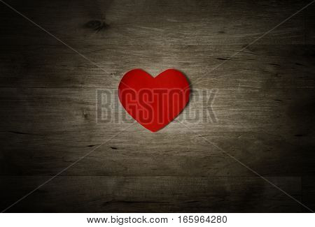 A red heart on old worn and weathered wood planking showing scuffs knots and scratches. Dark vignette. Love or Valentines Day concept.