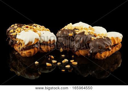 sweet cake with nuts on a black background with reflection