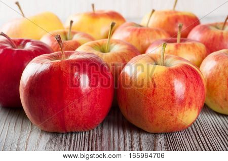 Ripe red apples on a wooden background.