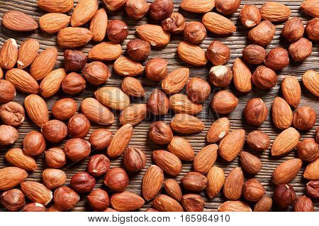 Almond and hazelnut on a wooden table. Background with nuts.