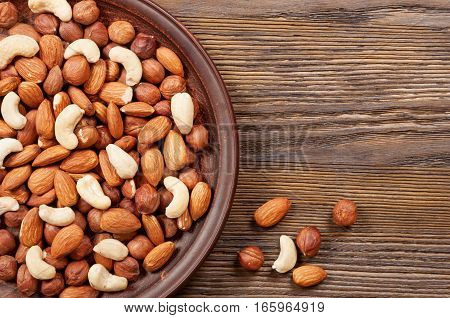 Different nuts in plate on a wooden background. Almond hazelnut and cashew.