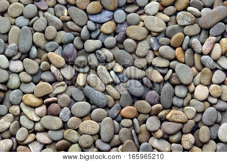 dark background of a smooth sea pebbles top view