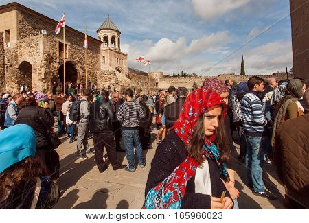 MTSKHETA, GEORGIA - OCT 14, 2016: Faces of people coming to the historical christian Svetitskhoveli Cathedral, built in 4th century on October 14, 2016. UNESCO World Heritage Site.