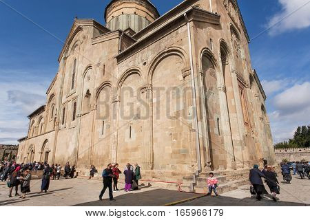 MTSKHETA, GEORGIA - OCT 14, 2016: Celebration of City Day in crowd near the historical christian Svetitskhoveli Cathedral, built in 4th century on October 14, 2016. UNESCO World Heritage Site.