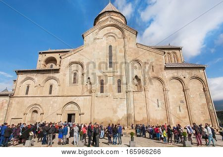 MTSKHETA, GEORGIA - OCT 14, 2016: Crowd celebrating the City Day past the historical christian Svetitskhoveli Cathedral, built in 4th century on October 14, 2016. UNESCO World Heritage Site.