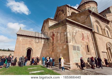 MTSKHETA, GEORGIA - OCT 14, 2016: Crowd of praying men and women around the walls of Svetitskhoveli Cathedral, built in 4th century on October 14 2016. UNESCO World Heritage Site.
