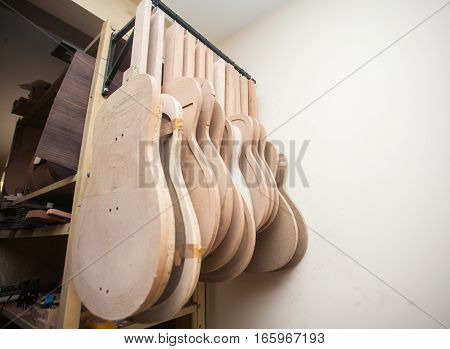 a row of classical unfinished guitar at workshop.