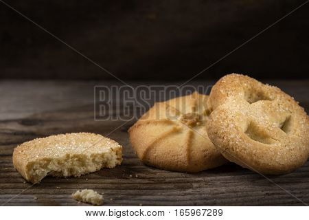 Butter cookies and crumbs over wooden background