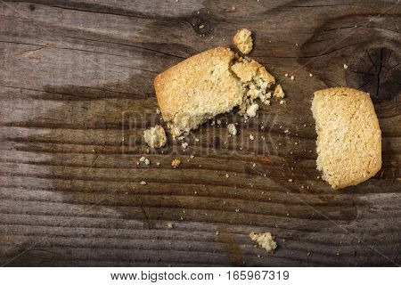 Broken butter cookies and crumbs over wooden background with copy space