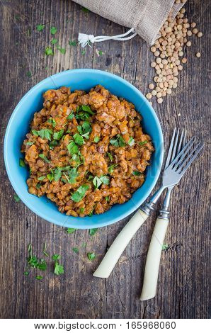 Frash lentil stew with bolognese sauce in a bowl with parsley on rustic wooden table. Italian food concept. Heathy vegetarian food. Top view.