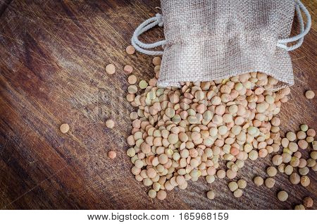 Brown dried lentils in a burlap bag on wooden board background with space for text. Dry Organic Brown Lentil. Healthy vegetarian food concept. Top view. Copy space.