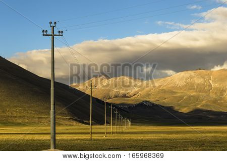 Famous mountain village of Castelluccio di Norcia with beautiful summer landscape at Piano Grande (Great Plain) mountain plateau in the Apennine Mountains on a cloudy day, Umbria, Italy. Low key.