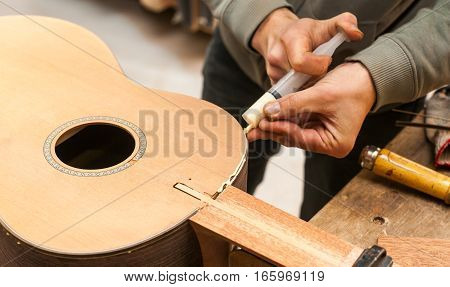 The worker glues guitar in the studio for the production of guitars.