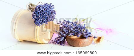 Making aroma bags bunch of dry wild mountain lavender flowers and wooden bowl banner background